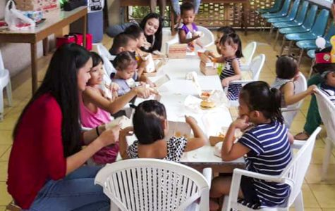 Krystelle and Arabella talk with children as they eat lunch.