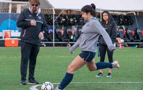 As her coaches watch, Ava Cholakian kicks a ball during practice.