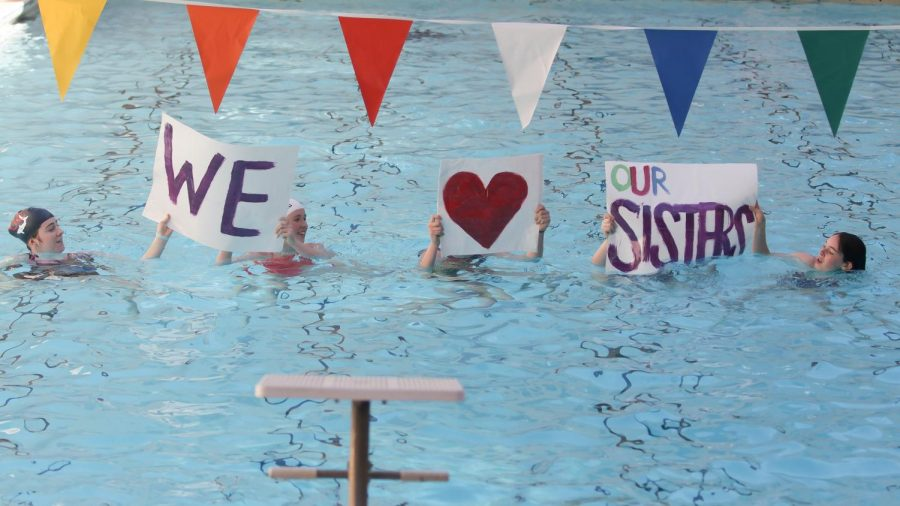 Students+perform+a+group+swim+routine+and+hold+posters+to+support+sister+classes.