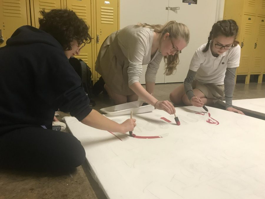 Juniors work together to sketch and paint their class backdrop.