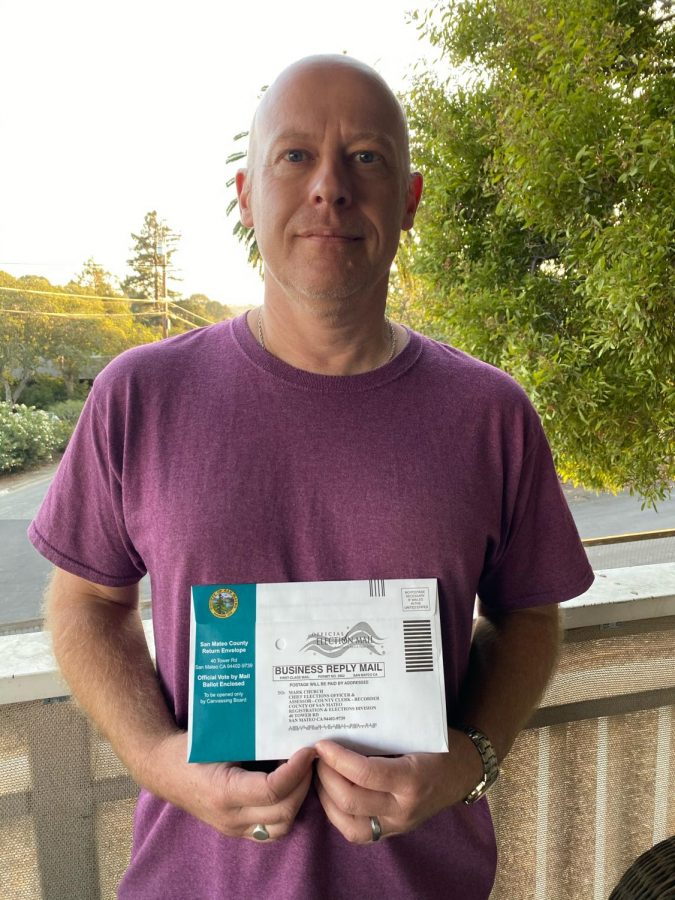 Photo of Mike Enock holding his mail-in ballot.