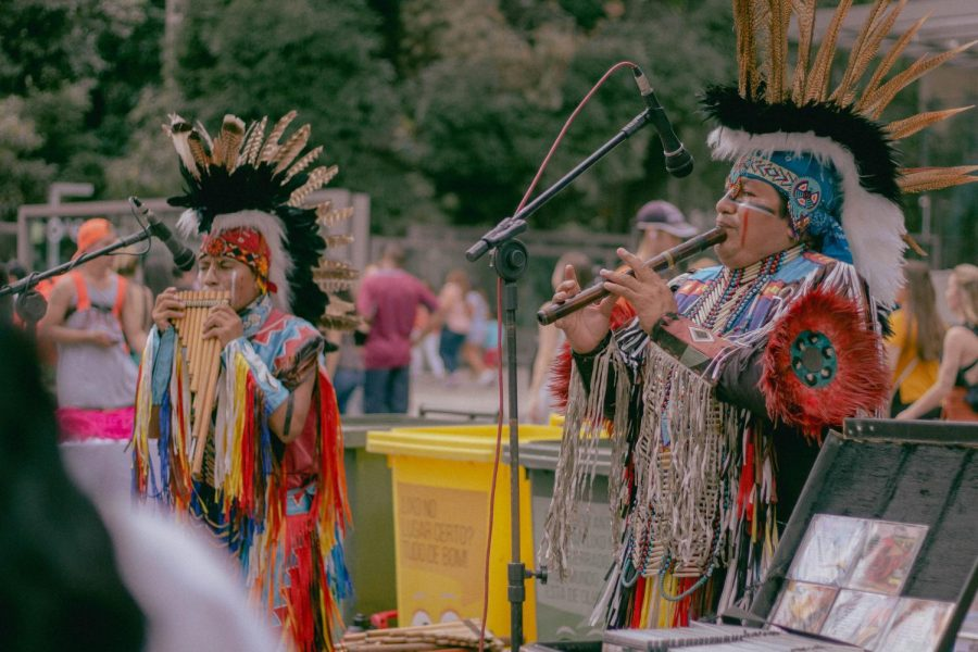 Native Americans playing traditional woodwind instruments