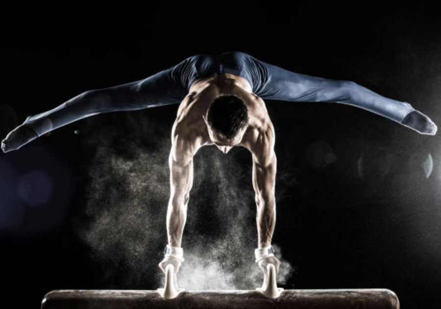 Male gymnast performing a handstand on a pommel horse.