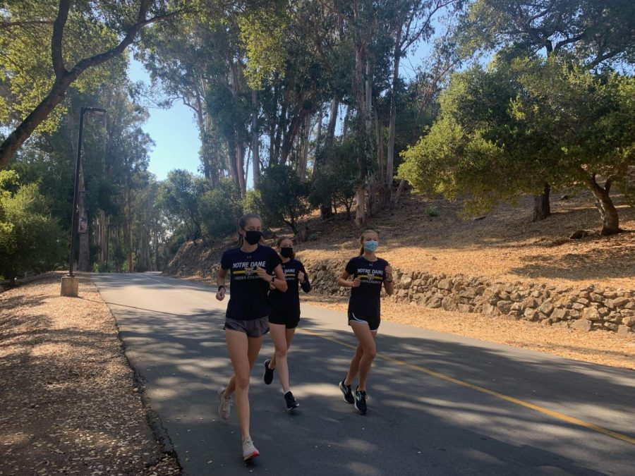 Kayla George (left), Annette Henderson and Helena Morell run through the Notre Dame de Namur campus during their cross country practice.